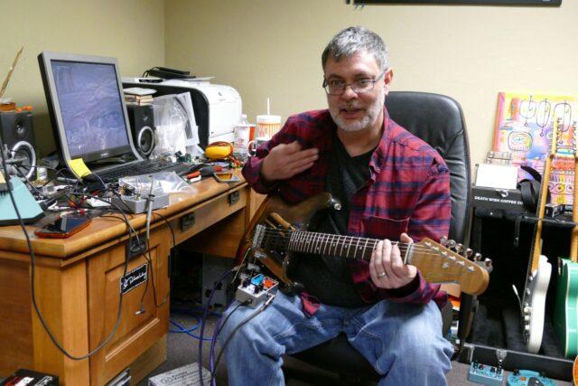 """Robert Keeley w swoim """"pokoju gry"""" (a gitara, którą trzyma w rękach, to replika Strata, którą Jimi Hendrix podpalił, a która została przywrócona do życia przez Franka Zappę)."""